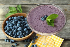 Purple smoothie made with blueberry. On wooden board Royalty Free Stock Photos