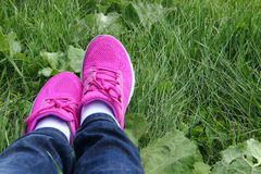 Purple sneakers on the grass. Break after a good walk royalty free stock images