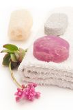 Purple soap and flower. Home spa with algae soap, loofa and towel royalty free stock photography