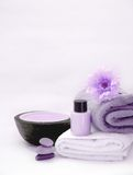 Purple Spa still life. On white spa towel and scented candle la stone therapy and flower Royalty Free Stock Image