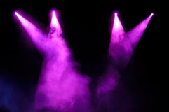 Purple Spotlights. Purple stage spotlights in smoke over black background stock photo