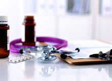 Purple stethoscope and pills on a laptop computer Royalty Free Stock Image
