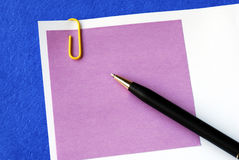 A purple sticky note. Isolated on blue royalty free stock photography
