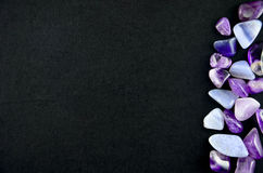 Purple stones on black background Stock Images