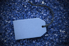 Purple Stones With Label And Copy Space Frame. One Blue Label Or Tag With Black Ribbon. Blue And Purple Small Stones As Background With Copy Space Your Text Here Stock Photos