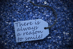 Purple Stones With Label Always A Reason To Smile. One Blue Label Or Tag With Black Ribbon On Blue And Purple Small Stones. Background With English Life Quote stock images