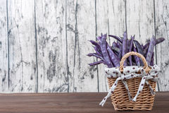 Purple string beans in a wicker basket. On a wooden background Royalty Free Stock Photography