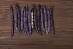 Purple string beans on a wooden background. Purple string beans on wooden background Stock Image