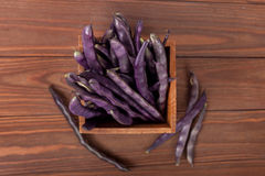 Purple string beans in a wooden box. Purple string beans on wooden background Royalty Free Stock Photos