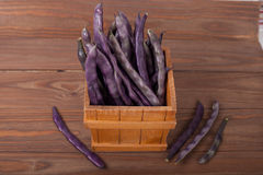Purple string beans in a wooden box. Purple string beans on wooden background Stock Photography