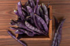 Purple string beans in a wooden box. Purple string beans on wooden background Royalty Free Stock Image