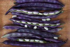 Purple string beans on a wooden plate on a wooden background. Purple string beans on wooden background Royalty Free Stock Image