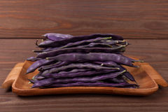 Purple string beans on a wooden plate on a wooden background. Purple string beans on wooden background Royalty Free Stock Photo