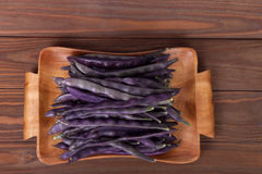 Purple string beans on a wooden plate on a wooden background. Purple string beans on wooden background Royalty Free Stock Photography