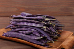Purple string beans on a wooden plate on a wooden background. Purple string beans on wooden background Royalty Free Stock Images