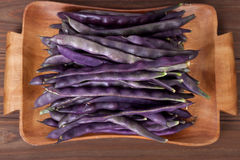 Purple string beans on a wooden plate on a wooden background. Purple string beans on wooden background Stock Image