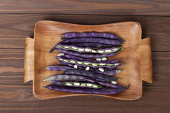 Purple string beans on a wooden plate on a wooden background. Purple string beans on wooden background Royalty Free Stock Photos