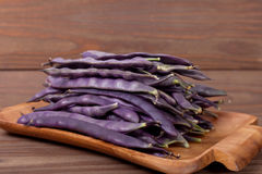 Purple string beans on a wooden plate on a wooden background. Purple string beans on wooden background Stock Photography