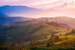Purple sunrise in foggy countryside. Distant mountains in blue shade. fantastic autumn mood stock images