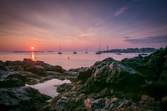 A Purple Sunrise over Lady Cove in Marblehead, MA. Purple skies at sunrise above anchored sailboats in Lady Cove at Devereaux Beach in Marblehead, Massachusetts Royalty Free Stock Images