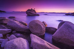 Purple sunset. Lake Tahoe in purple sunset with boulders and rocks Royalty Free Stock Photography