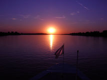 Purple sunset. Over calm river from boat with flag Royalty Free Stock Photography