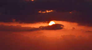Purple sunset. Dark clouds and sun disk Royalty Free Stock Image