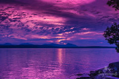 Purple sunset ocean sky. Purple clouds and the sky, mountains in the ocean Stock Photos
