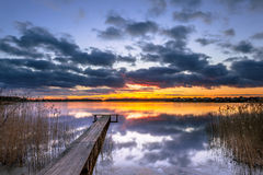 Purple Sunset over Tranquil Lake with Reed and Wooden Jetty Royalty Free Stock Image