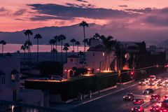 Purple sunset in Santa Monica with palms and traffic on freeway stock images