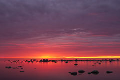 Purple sunset at sea. A photo of a purple sunset at sea full of stones. Due to cloudy sky, the sky was painted to purple, red and violet by the sun Royalty Free Stock Photography