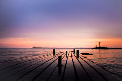 Purple sunset on sea with pier Stock Images