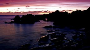 Purple Sunset with unique rocks Stock Image