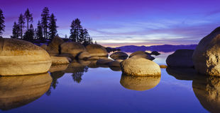 Purple Tahoe Sunset. Sunset at Sand Harbor, Lake Tahoe, Nevada.  Large granite boulders reflecting into glassy water with warm light