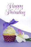 Purple theme cupcake with orchid flower with Happy Thursday sample text. Or copy space for your text here stock image
