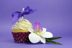Purple theme cupcake with orchid flower Stock Photos