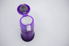 Purple thermocup with hot tea in the snow Stock Image