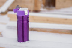Purple thermocup with hot tea in the snow Stock Images