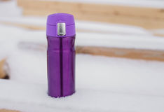 Purple thermocup with hot tea in the snow Royalty Free Stock Photos