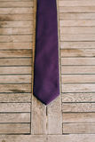 Purple tie on wooden background Royalty Free Stock Photos
