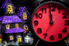 Purple toy ghost house with red halloween alarm clock Stock Photo