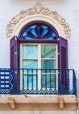 Purple traditional window in Spain wit stucco decoration. Traditional window and balcony in Spain wit stucco decoration and plaster royalty free stock photo