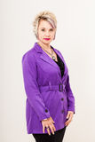 Purple trench coat. A caucasian woman with bright magenta lips posing confidently in a vibrant purple trenchcoat standing infront of a light gray background Royalty Free Stock Images