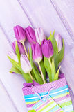 Purple tulip bouquet in gift bag. Over wooden table Royalty Free Stock Images