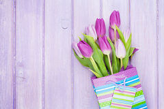 Purple tulip bouquet in gift bag. Over wooden table with copy space Stock Photos