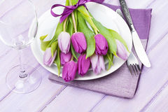 Purple tulip bouquet over plate on wooden table Stock Images