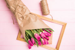 Purple tulip bouquet with tie on frame on pink background. Top view over pink wooden table Stock Photography