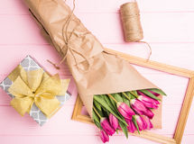 Purple tulip bouquet with tie on frame with present on pink background. Top view over pink wooden table. Pink tulips in Royalty Free Stock Photography
