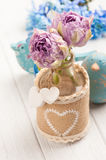 Purple tulips in bottle with hearts Royalty Free Stock Photography