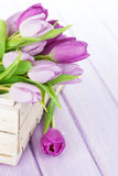Purple tulips box over wooden table Stock Photo